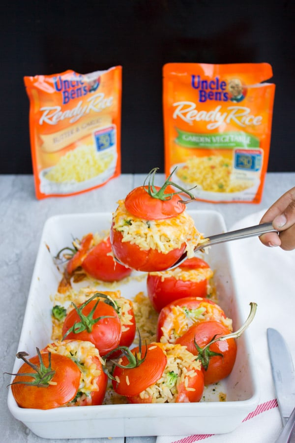 a cheese-topped Broccoli Rice Casserole Stuffed Tomato balanced over a casserole dish with more stuffed tomatoes