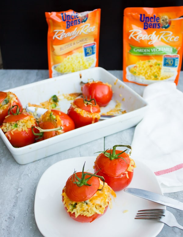 Two Broccoli Rice Casserole Stuffed Tomatoes on a white plate in front of a casserole dish with more stuffed tomatoes