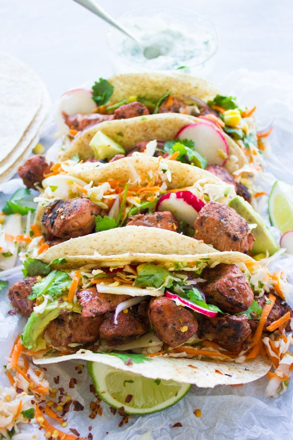 close-up of four tandoori chicken tacos filled with cilantro corn slaw with a small dish with yogurt dip in the background