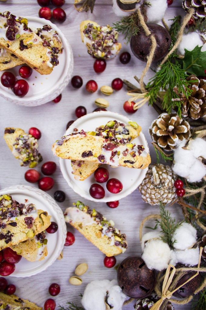 Two pieces of Cranberry Pistachio Biscotti on a plate surrounded by cranberries.