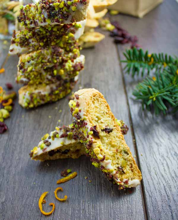 close-up of two Cranberry Pistachio Biscotti dipped in white chocolate glaze