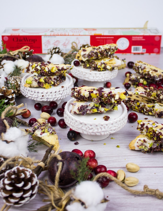 A collection of the biscotti cookies with crnaberry pistachip biscotti surrounded by holiday wreath