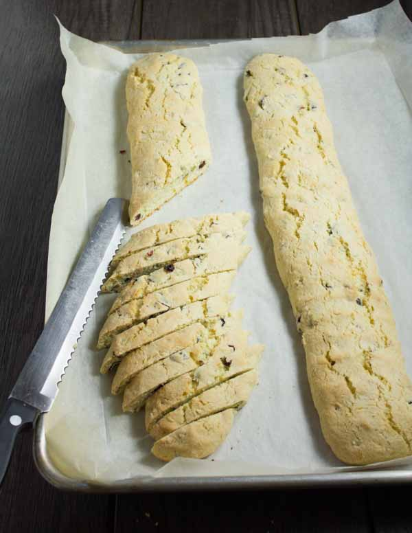 pistachio and cranberry biscotti being cut from a log of pre-baked batter