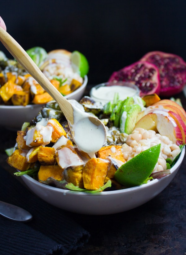 easy Tahini Dressing being drizzled on top of Lentil Fall Harvest Buddha Bowl.