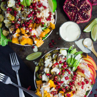 Lentil Fall Harvest Buddha Bowl. This easy, crazy delicious Buddha goodness bowl is all you need to make your life happier! Loaded with greens, lentils, navy beans, apples, avocado, sweet potatoes, sprouts, pomegranate arils--all drizzled with the perfect tahini sauce! Get this recipe and tips for Buddha bowl perfection. www.twopurplefigs.com