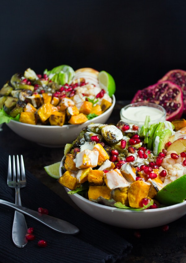 Lentil Fall Harvest Buddha Bowls drizzled with tahini dressing and sprinkled with pomegranate arils