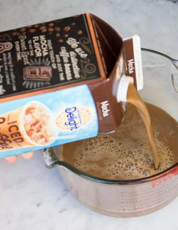 iced coffee being poured into a measuring cup