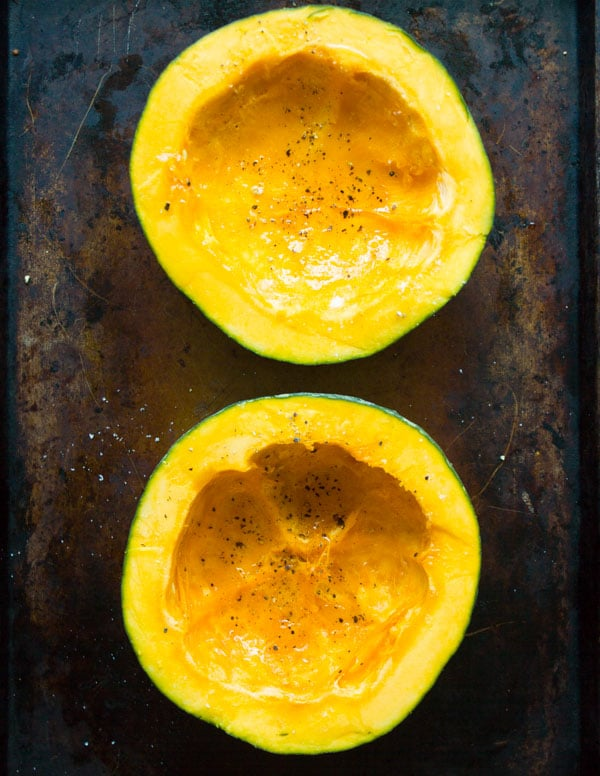 a halved kabocha squash on a baking sheet cut side up