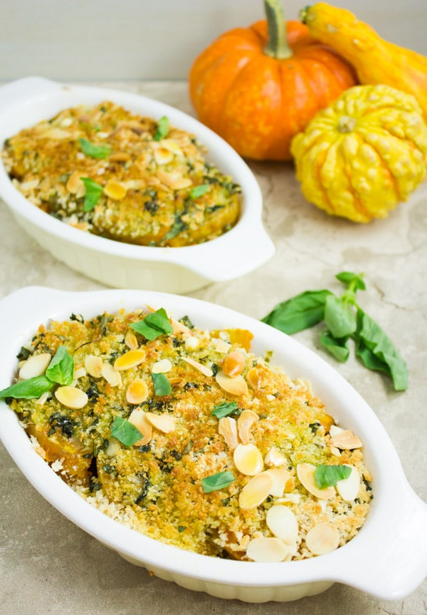 two individual casseroles of Roasted Butternut Squash Gratin topped with breadcrumbs and slivered almonds