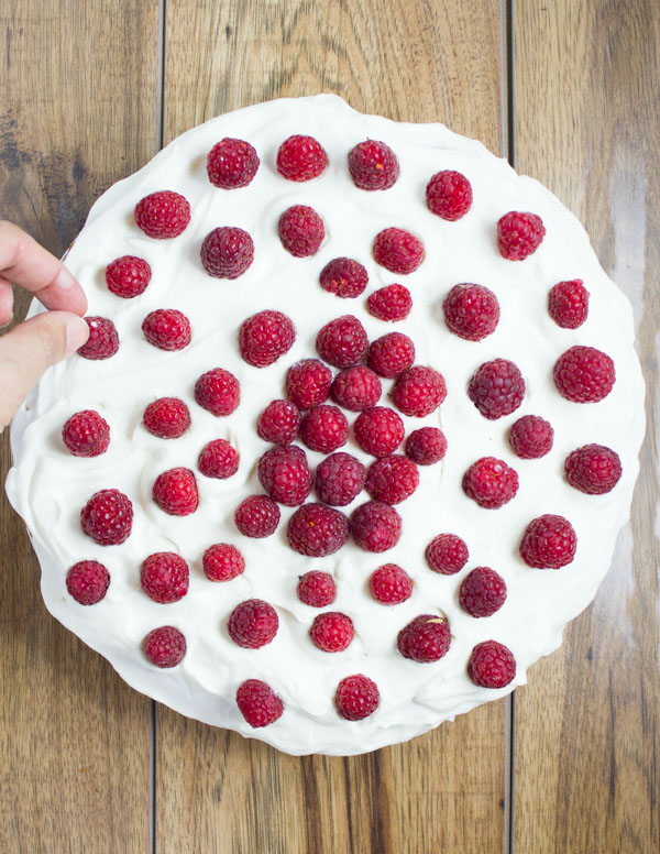 a vanilla cream cake being topped with fresh raspberries