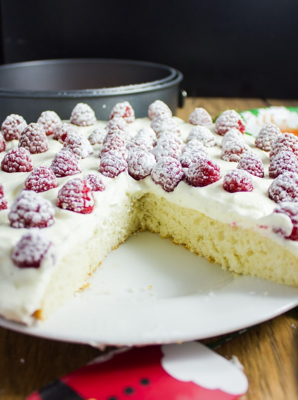 side view of a Fluffy White Raspberry Holiday Cake with a big piece cut out the front
