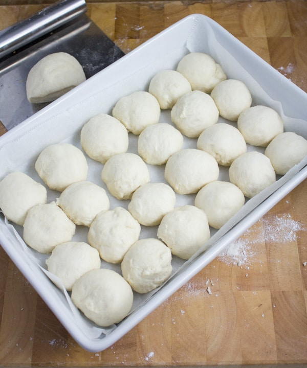 individual dinner rolls proofing in a pan before baking