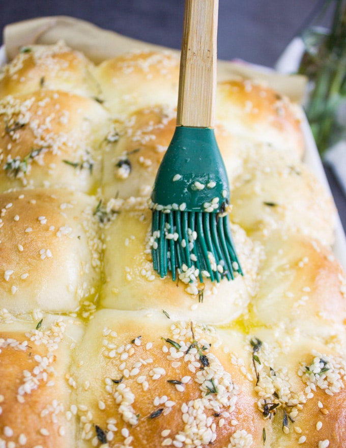 brushing dinner rolls with butter mixture