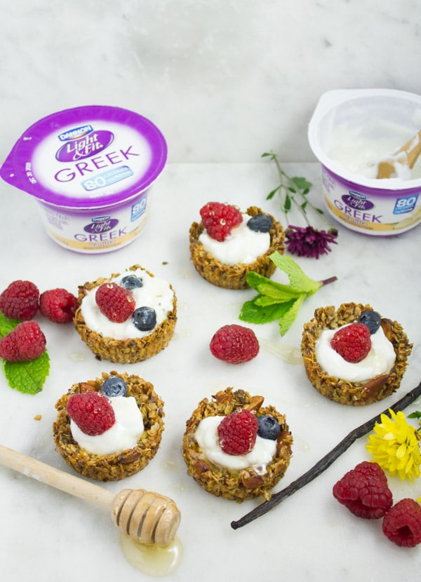 Healthy Breakfast Granola cups filled with yogurt and fresh berries and drizzled with honey