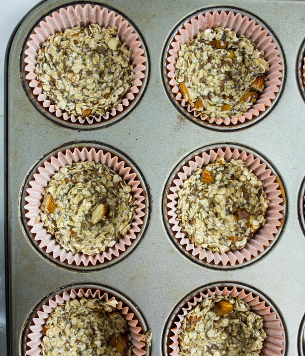 granola being pressed into muffin tins to make granola cups