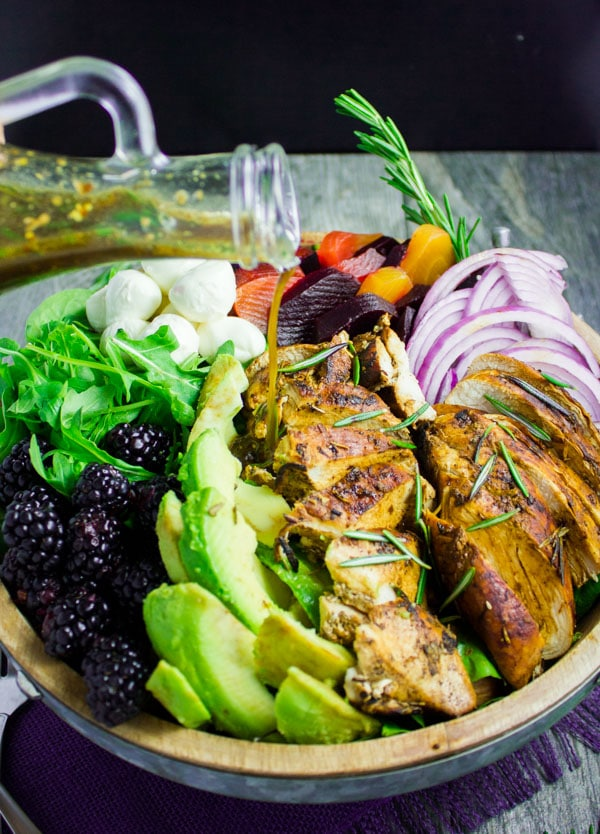 side view of a bowl of Chicken Salad with balsamic marinated chicen breast, blackberries and avocados
