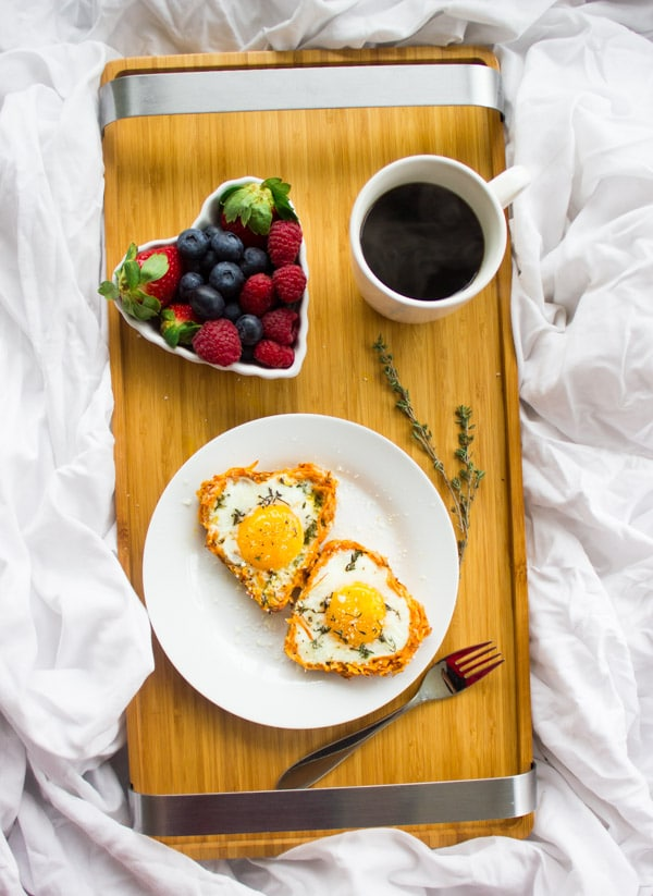 Baked Eggs in Sweet Potato Crusts served on a breakfast tray with a side of berries and a cup of coffee