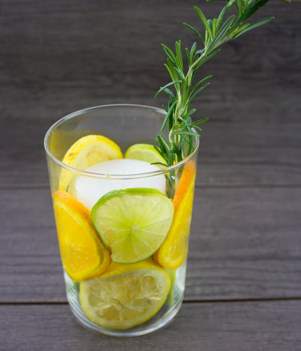 citrus fruit candle holder with a sprig of rosemary