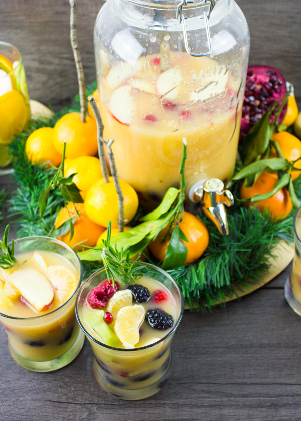 Fruity Non-Alcoholic Sangria with plenty of fruit served in glasses with a big mason jar of sangria in the back