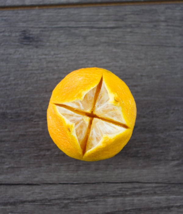 a tangerine being turned into a candle