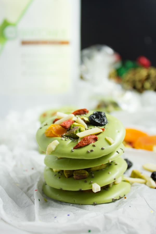 side view of stacked round Matcha White Chocolate Bark topped with dried fruits