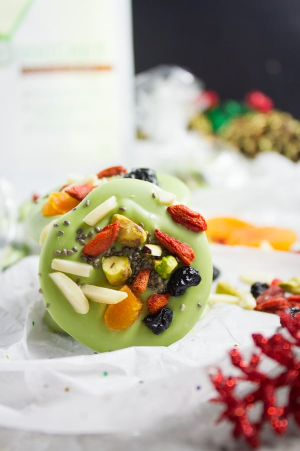 round pieces of Superfood Matcha Green Tea White Chocolate Bark on parchment paper