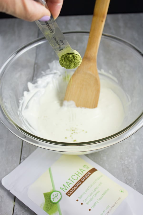 matcha green tea powder being added to melted white chocolate