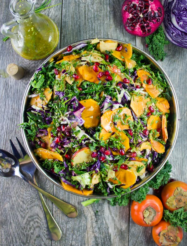 overhead shot of a big bowl of kale salad with apples, persimmon, shredded cabbage and pomegranate seeds with a dressing decanter and some salad ingredients in the background.