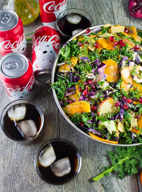 partial view of kale salad with apples, with some coke cans and filled glasses with coca-cola on the side