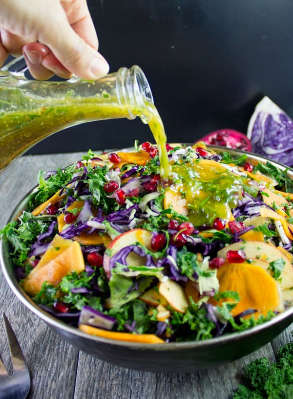 Coca-Cola Dressing being poured over a bowl with kale salad with apples, pomegranate seeds and shredded cabbage.