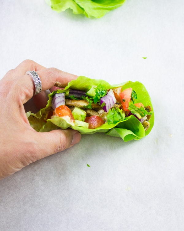 a hand holding a Chicken Shawarma Lettuce Cup against a white backdrop