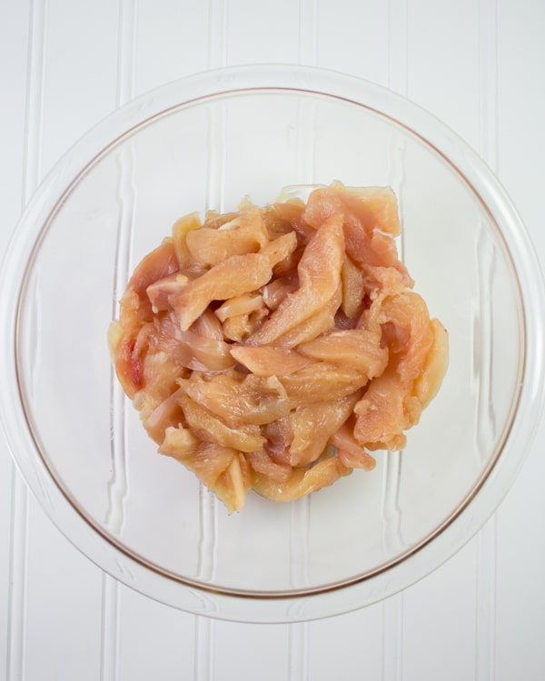 strips of skinless, boneless chicken in a glass bowl ready for seasoning