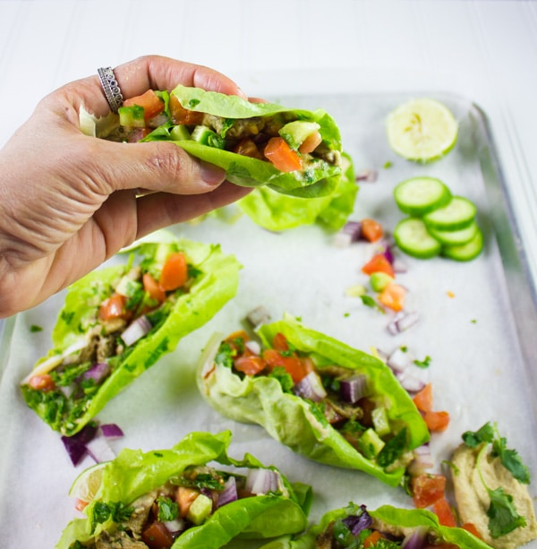a hand holding a chicken shawarma lettuce cup against the backdrop of a sheet pan with more lettuce cups