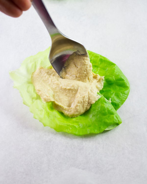 lettuce leave with a dollop of hummus as the base for a chicken lettuce wrap