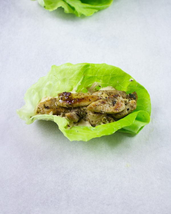 Chicken Shawarma placed on top of a dollop of hummus on a lettuce leave