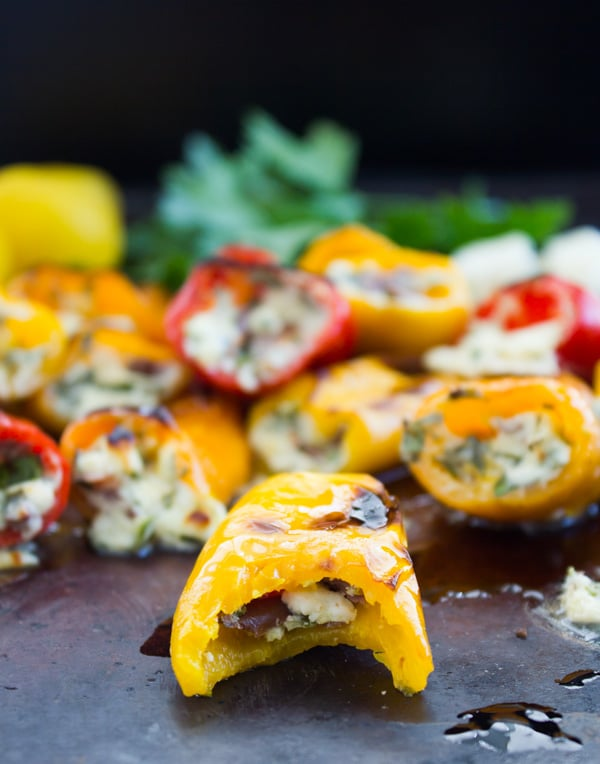 a bite-sized feta stuffed bell pepper on a baking sheet with one bite taken out the front