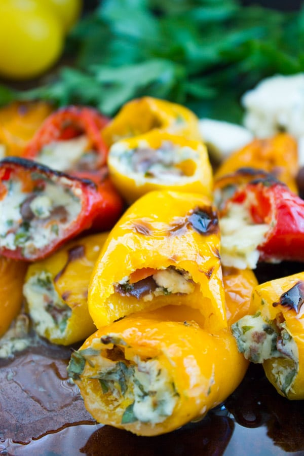 close-up of Mini Zesty Feta Stuffed Peppers arranged on a baking sheet with fresh herbs in the background