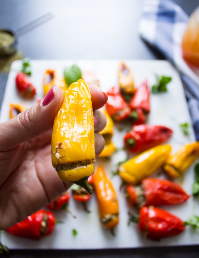 A hand holding a mini yellow stuffed pepper recipe