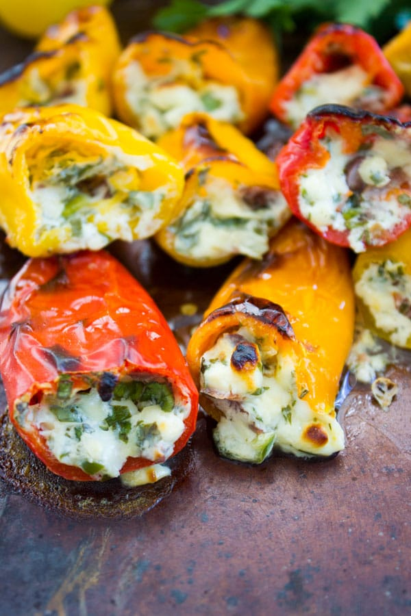 slightly charred bite-sized Feta Stuffed Peppers arranged on a baking sheet