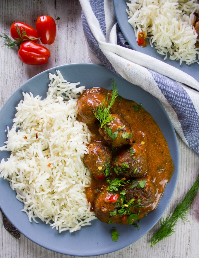 One plate of kofte turkish meatballs over rice in a tomato sauce