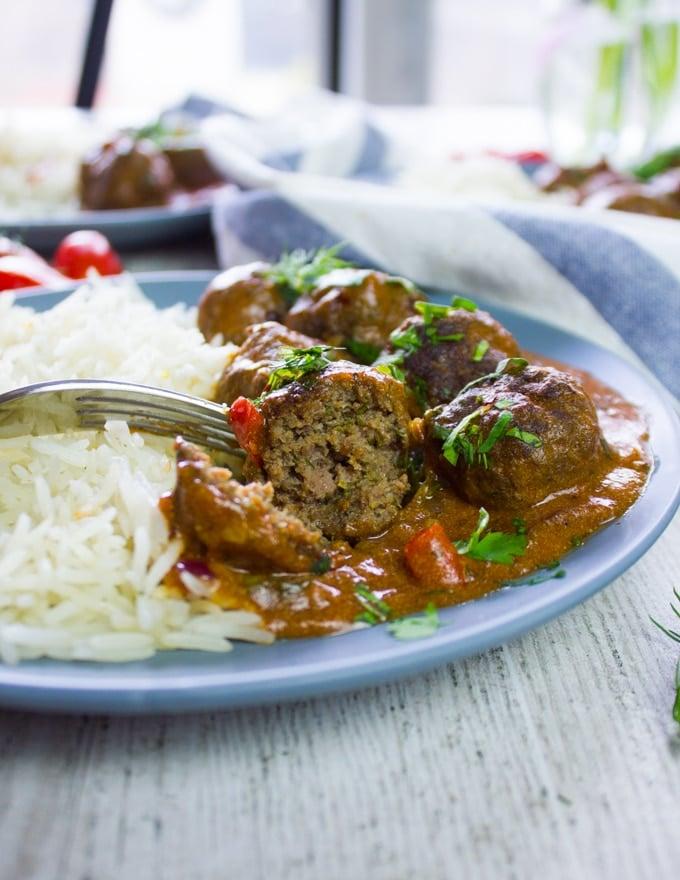 A fork holding a bitten piece of kofte turkish meatballs showing how juicy it is