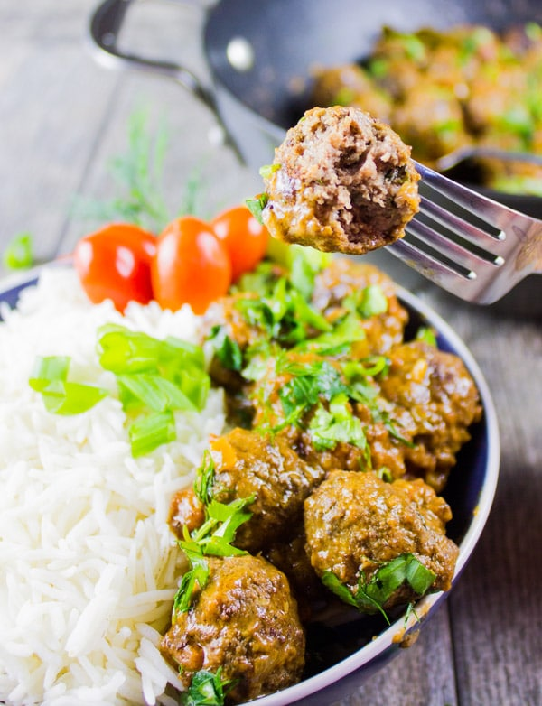 a fork spiking a Turkish meatball over a plate of more meatballs and rice