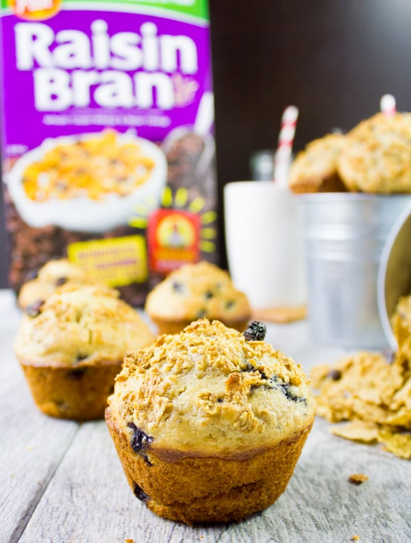 side view of raisin bran muffin with a box of raisin bran in the background