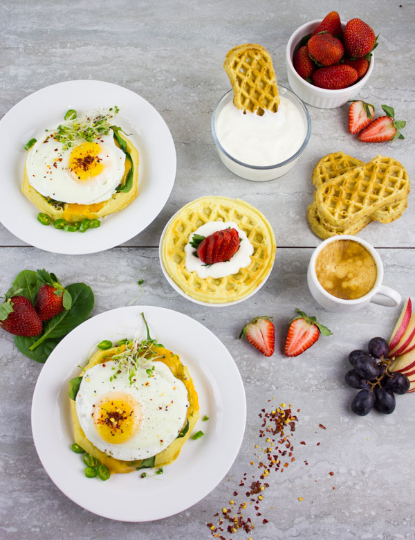 Cheesy Spinach Egg Breakfast Waffles served on 2 plates on a breakfast table with some fresh fruit and bowl of yogurt as additional toppings