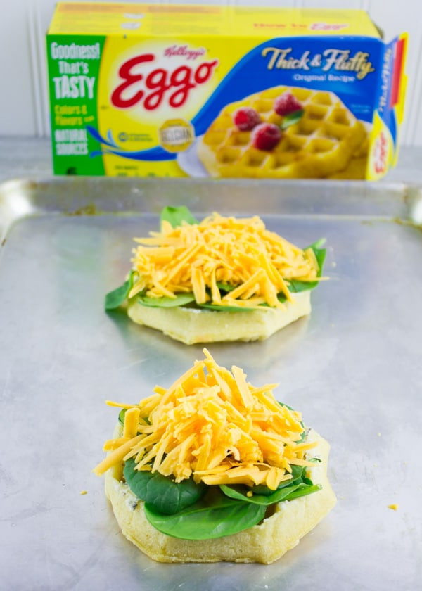 a breakfast waffle topped with fresh spinach and grated cheddar cheese