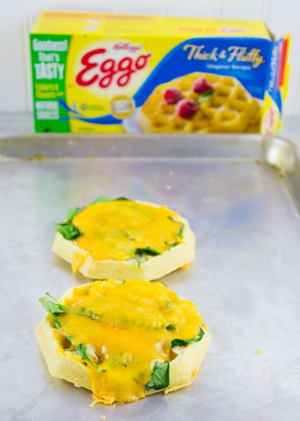 breakfast waffles topped with spinach and melted cheddar cheese