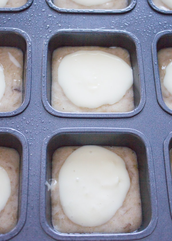 banana bread muffins batter being topped with a cream cheese layer