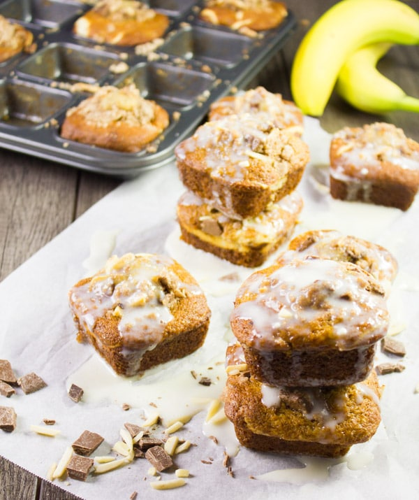 glazed cream cheese banana bread muffins on a sheet of parchment paper