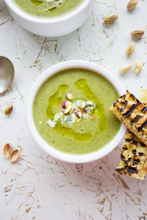 overhead of a white bowl of Blue Cheese Broccoli Soup with some toasted bread sticks and unshelled pistachios on the side