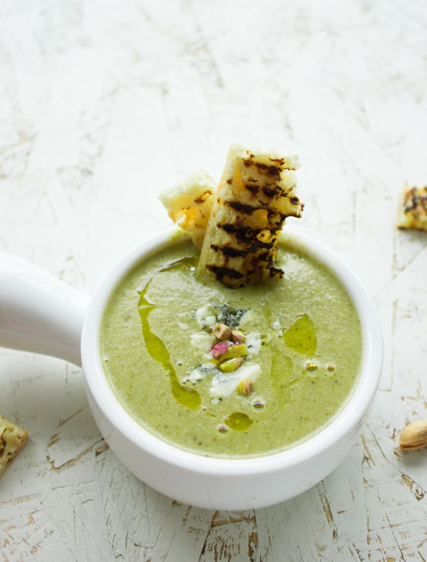 a bowl of Smooth Blue Cheese Broccoli Soup topped with pistachios and a drizzle of olive oil